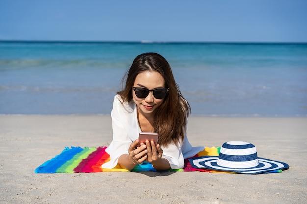 彼女のスマートフォンと熱帯の砂浜、夏休みのコンセプトで日光浴を使用して若いアジアの女性旅行者