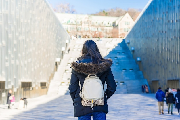 Young asian woman traveler with backpack traveling into the ewha womans university in seoul, south korea