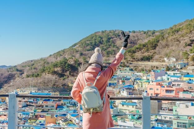 Молодой азиатский путешественник женщины с рюкзаком путешествуя в деревню культуры gamcheon расположенную в пусане, южной корее