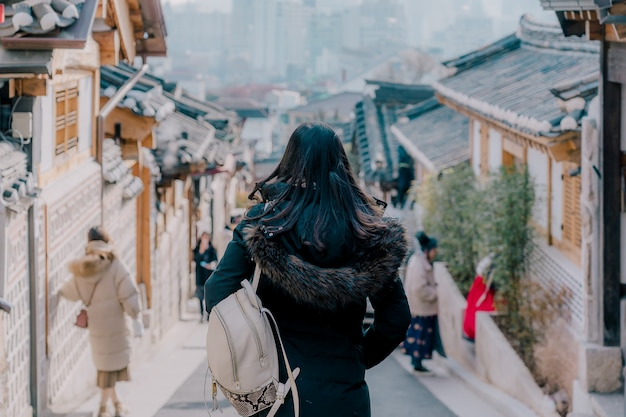 Young asian woman traveler with backpack traveling into the traditional korean style architecture