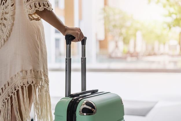 Молодая азиатская женщина-путешественница с багажом на тропическом курорте возле пляжа