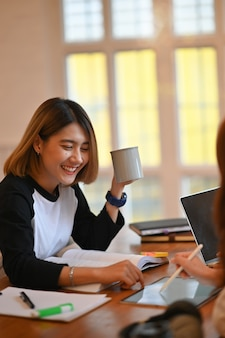 Young asian woman tutoring friend on wood table.