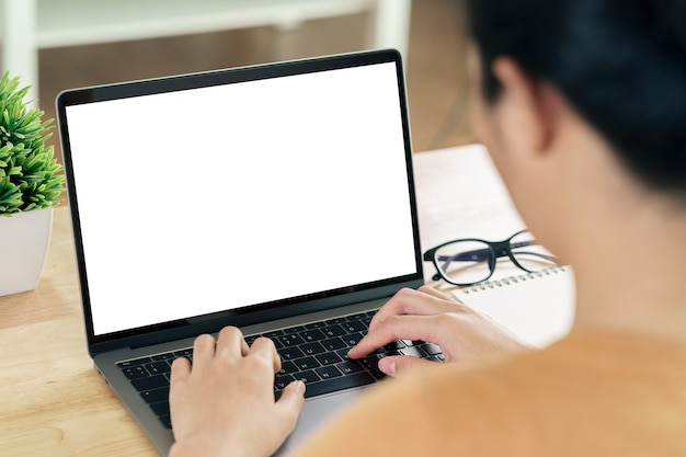 Young asian woman typing laptop computer keyboard with white blank screen on the table. working at home, relaxing, online shopping, communication and technology concept
