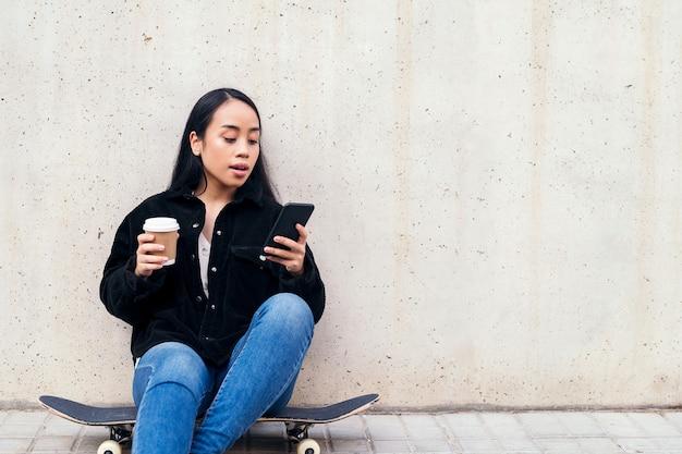 콘크리트 벽에 기대어 스케이트보드를 타고 야외에 앉아 전화를 하는 젊은 아시아 여성