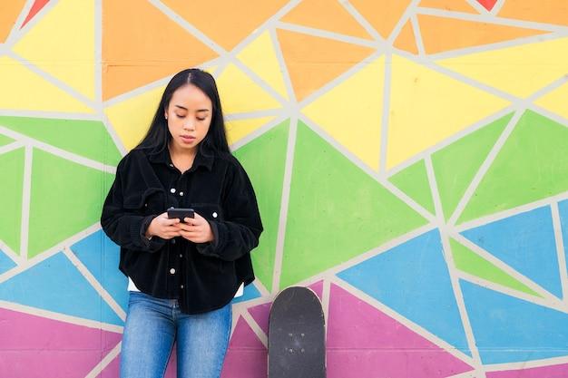 스케이트보드 옆에 있는 화려한 벽에 기대어 휴대폰으로 타이핑하는 젊은 아시아 여성