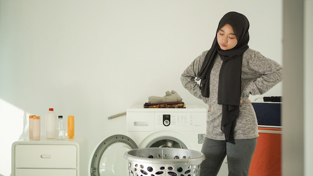 Young asian woman upset to see dirty clothes basket at home