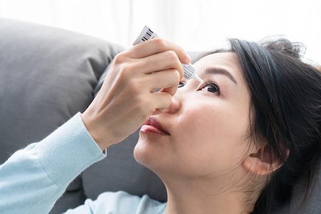 젊은 아시아 여성은 눈 치료를 위해 안약을 사용합니다. 충혈, 안구 건조, 알레르기 및 눈 가려움증. 시력 및 안과 의학 개념입니다.