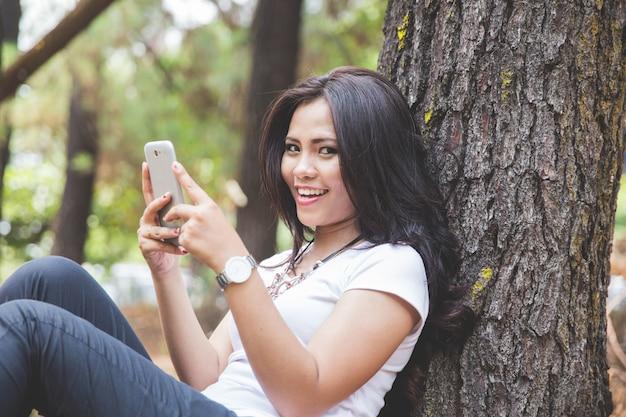 야외에 앉아있는 동안 핸드폰을 사용하는 젊은 아시아 여성