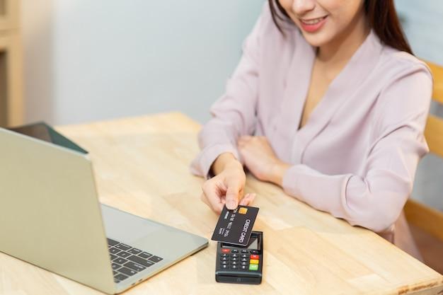 신용 카드와 컴퓨터 노트북을 사용하여 온라인 쇼핑을 하는 젊은 아시아 여성