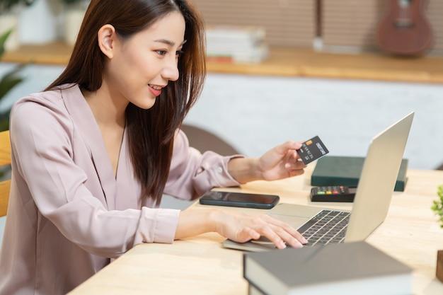 オンラインショッピングにクレジットカードを使用して若いアジア女性