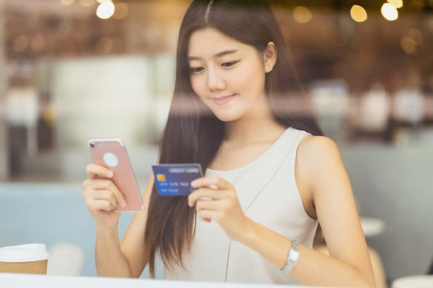 Young asian woman using credit card with mobile phone for online shopping in coffee shop or coworking space beside window mirror, technology money wallet and online payment concept, credit card mockup