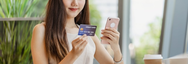 Young asian woman using credit card with mobile phone for online shopping in coffee shop
