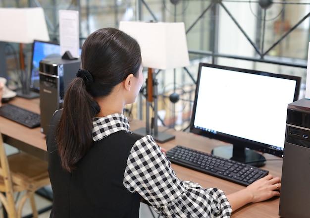 ライブラリーでデスクトップコンピュータを使用している若いアジア人女性