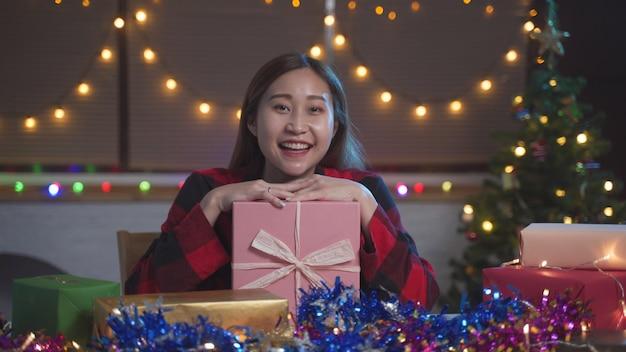 크리스마스와 새해 파티를 축하하기 위해 가족과 화상 통화를 하기 위해 노트북을 웹캠으로 사용하는 젊은 아시아 여성