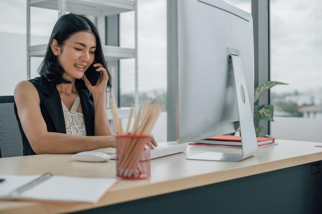Молодая азиатская женщина, использующая портативный компьютер и разговаривающая по телефону