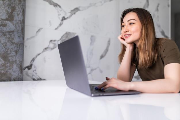 부엌에서 랩톱 컴퓨터를 사용하는 젊은 아시아 여성