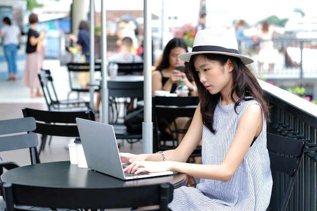 Young asian woman using laptop computer sitting at cafe outdoors, people and technology