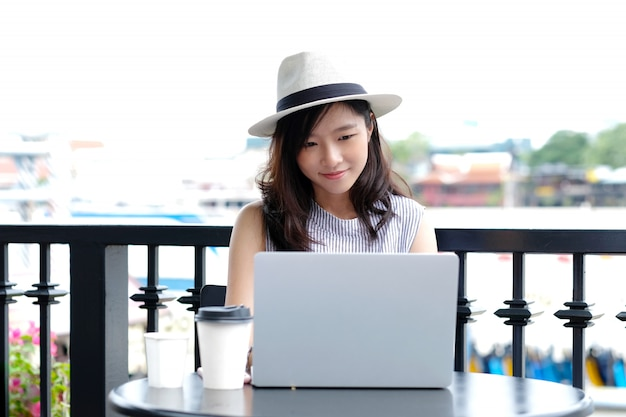 Young asian woman using laptop computer sitting at cafe outdoors