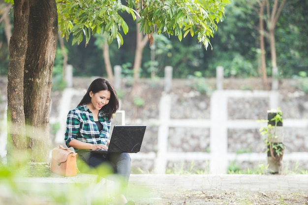 Young asian woman using laptop while sitting on the park