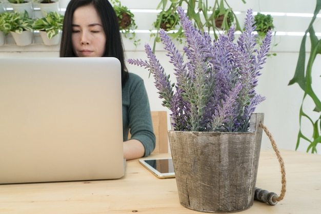 Young asian woman using laptop on wood table