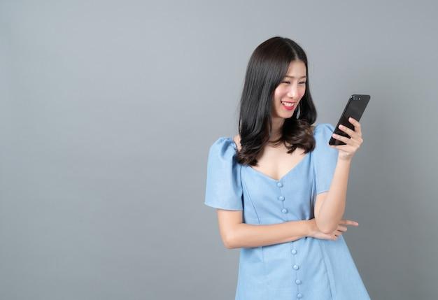 회색 벽에 파란 드레스에 행복한 얼굴로 휴대 전화를 사용하는 젊은 아시아 여자