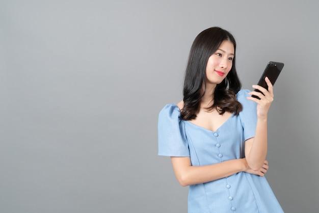 青いドレスで幸せそうな顔で携帯電話を使用して若いアジアの女性