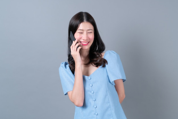 幸せそうな顔で携帯電話を使用して若いアジアの女性