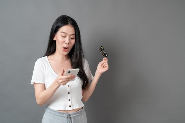 クレジットカードを持っている手で電話を使用して若いアジアの女性-オンラインショッピングの概念