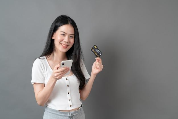 Молодая азиатская женщина, использующая телефон с рукой, держащей кредитную карту