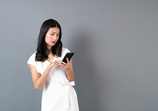 Young asian woman using phone with sulk face on grey