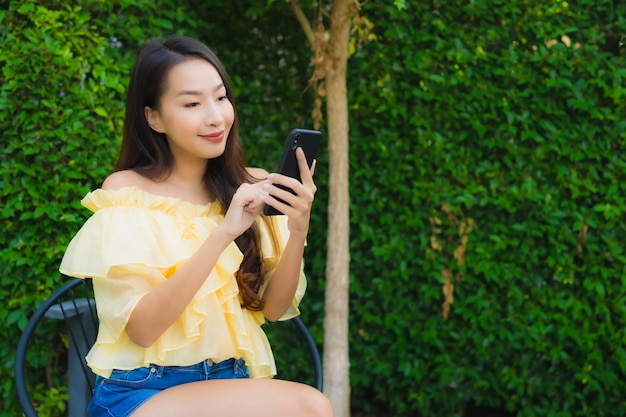 Young asian woman using smart mobile phone around outdoor nature