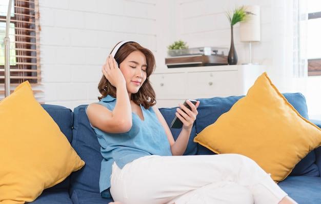 スマートフォンを使い、週末にリビングルームのソファに座ってヘッドフォンに接続して音楽を聴く若いアジア人女性。