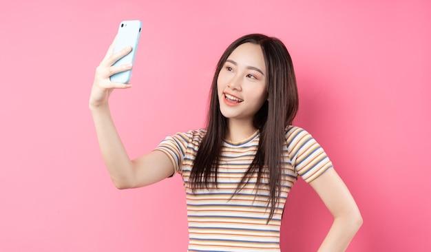 ピンクのスマートフォンを使うアジアの若い女性