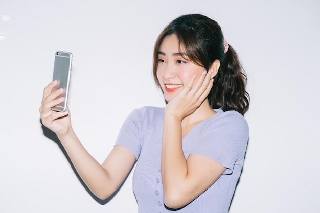 白のスマートフォンを使用して若いアジアの女性