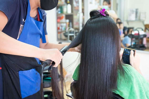 Young asian woman using smartphone while she getting a straight hair with hair straightener by hairdresser. beauty salon, hair care concept.