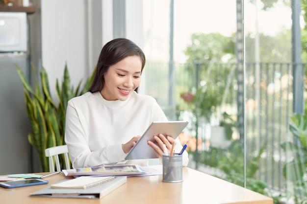 現代のオフィスで彼女のオフィスの机に座ってスマートフォンを使用して若いアジアの女性