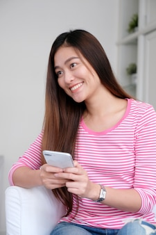 Young asian woman using smartphone in white room background,