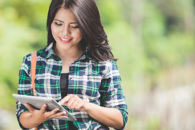 Young asian woman using a tablet pc while walking on the park