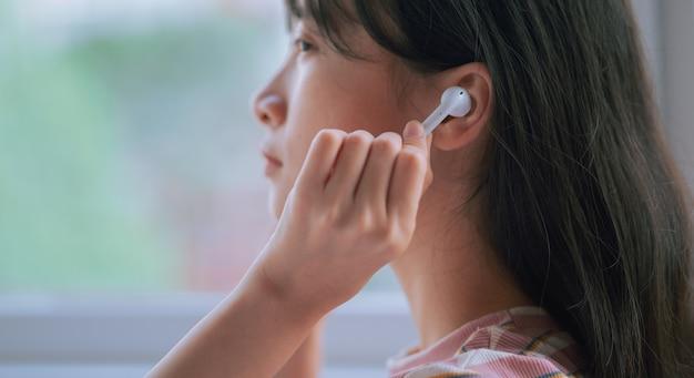 音楽を聴くためにワイヤレスイヤホンを使用して若いアジアの女性
