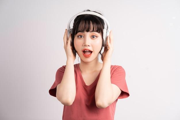 音楽を聴くためにワイヤレスヘッドフォンを使用して若いアジアの女性