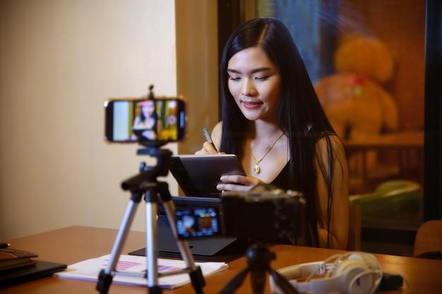 Молодая азиатская женщина-влогер, записывающая видеоконтент для онлайн-канала, женщина смотрит в камеру и разговаривает о видеосъемке, создатель контента или концепция социального влиятельного лица