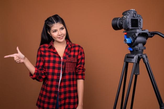 삼각대에 카메라와 함께 스튜디오에서 vlogging 젊은 아시아 여자