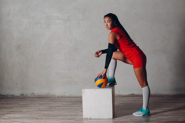 Young asian woman volleyball player in red uniform with ball