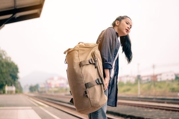 철도 플랫폼에서 기차를 기다리는 젊은 아시아 여성. 관광, 여행 및 레크리에이션의 개념입니다.
