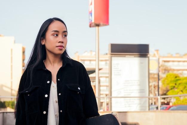 젊은 아시아 여성이 지하철 역 출구에서 기다립니다. 도시 생활 방식의 개념