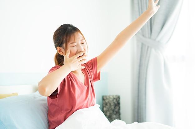 若いアジアの女性は早朝に目を覚ます