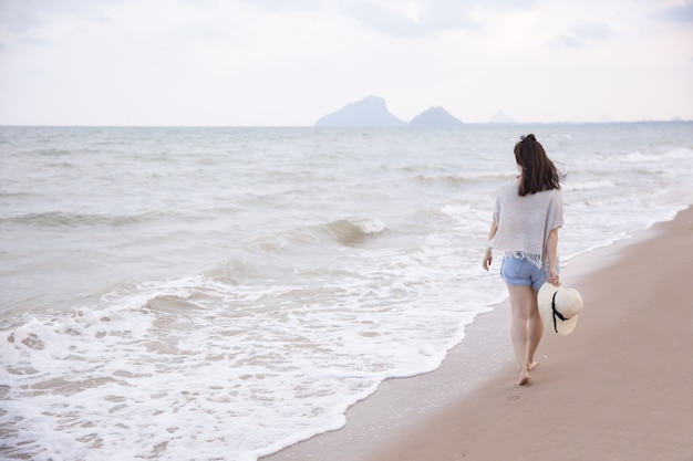 Молодая азиатская прогулка женщины на пляже в таиланде