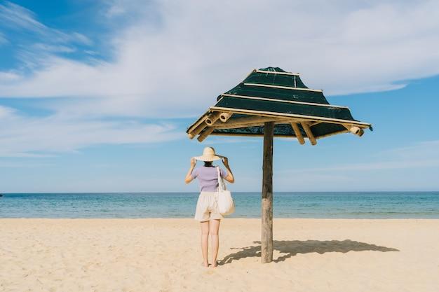 熱帯のビーチを歩く若いアジアの女性