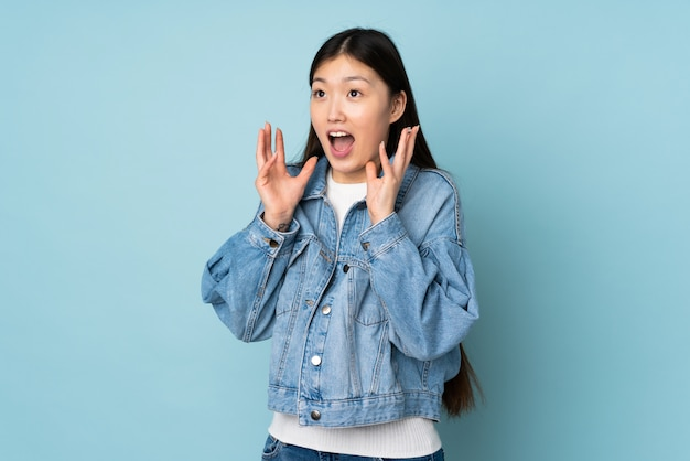 Young asian woman on wall with surprised facial expression