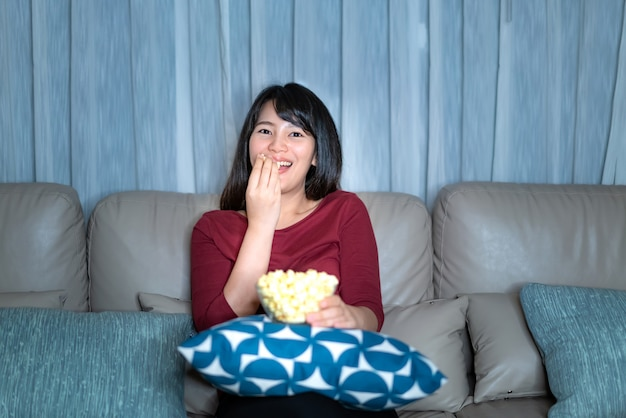 Young asian woman watching television suspense movie or news looking happy eating popcorn late night at home living room couch.